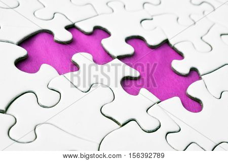A close up view of a white jigsaw puzzle with two missing puzzle pieces.