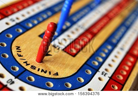 A close up image of a wooden cribbage board with a red cribbage peg in the winning position.