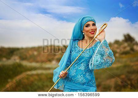 Oriental beauty Sa'idi dance. Nice girl wearing a national costume dancing shepherdess with shepherd's cane outdoors. Nomads.