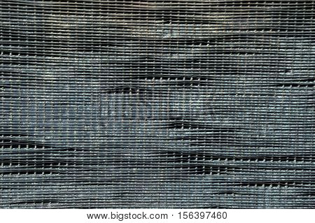 Close up of gray tin metal mesh or screen with areas of damage, disrepair and holes. Photographed in natural light.