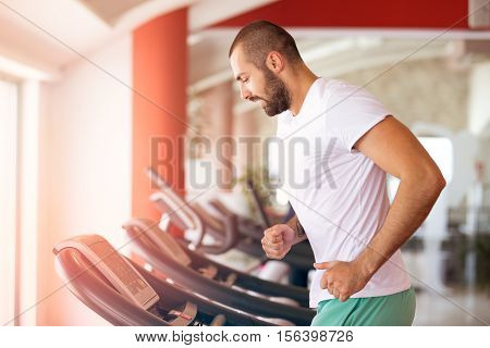 Man running in a modern gym on a treadmill concept for exercising, fitness and healthy lifestyle