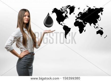 A beautiful businesswoman standing with a big oil drop above her open palm on the white background with the black outlines of the continents. Oil and petroleum products. The most valuable commodities of our lifetime. Black gold. Resource extraction.