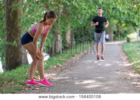 Man helps to woman with injured knee at sport activity.