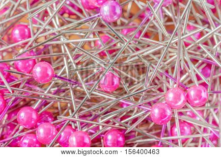 Blurred photo of stack of pink sewing pins in the box.