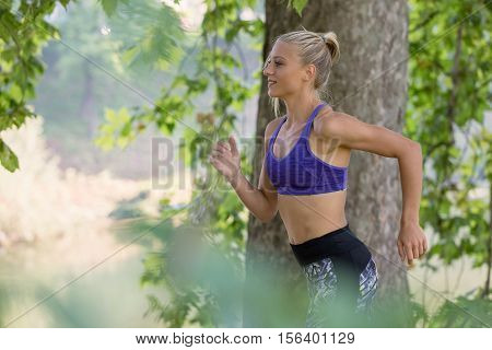 Jogging woman running in park in sunshine on beautiful summer day. Sport fitness model of Caucasian ethnicity training outdoor for marathon.