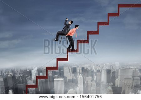 Image of businessman looking through binocular and sitting on a chair while his employee bringing chair on the stair