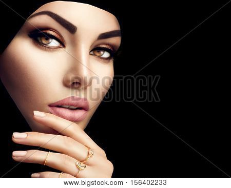 Beautiful Muslim Woman face portrait. Hijab. Close up of beauty arabian woman with perfect makeup and manicure isolated on black background. Traditional muslim dress, hijab, burka, niqab