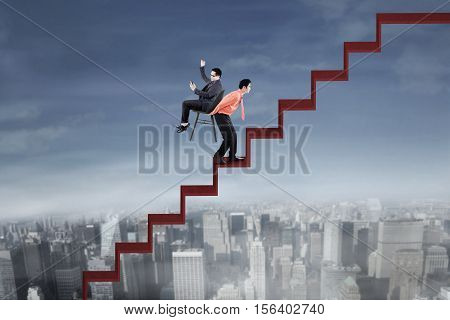 Portrait of success businessman using cellphone and sitting on the chair while his employee lifting a chair on the red stair