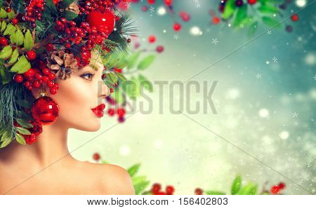 Christmas fashion model woman. Xmas New Year hairstyle and make up. Beauty Girl portrait. Winter Lady with Christmas decorations on head, baubles, professional makeup, red lips. On snowy background