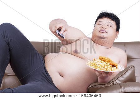 Portrait of lazy fat man sitting on the sofa while watching tv and holding junk food