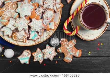 Christmas sweets baking gingerbread cookies on plate. Decorated for Christmas gingerbread cookies christmas bumps. Christmas cookies gingerbread on black table hot chocolate. New Year food. Top view