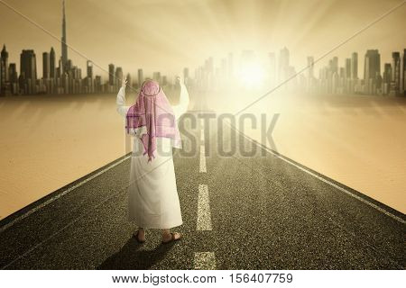 Image of muslim man prays on the road while wearing muslim clothes
