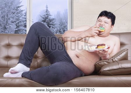 Obesity man eating a plate of donuts while sitting on the sofa in winter season