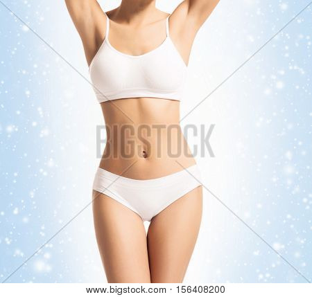 Young, sporty, fit and beautiful girl in sporty underwear over Christmas background with snow.