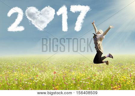 Image of attractive woman jumping on a flowers field with clouds shaped love and number 2017 in the clear sky