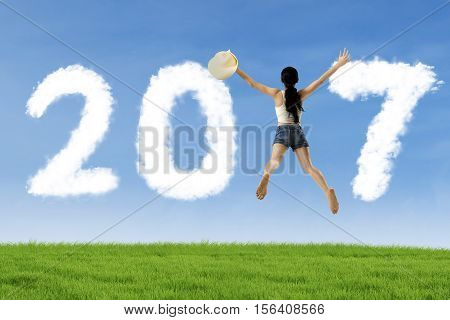 Image of woman holding hat and leaping with number 2017 on the meadow