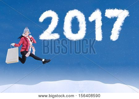 Young woman leaping on the sky with clouds shaped number 2017 while carrying shopping bag