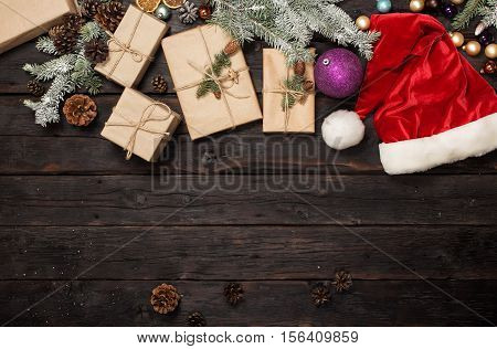 Christmas gift with santa hat and branches of fir on wooden table with copy space top view