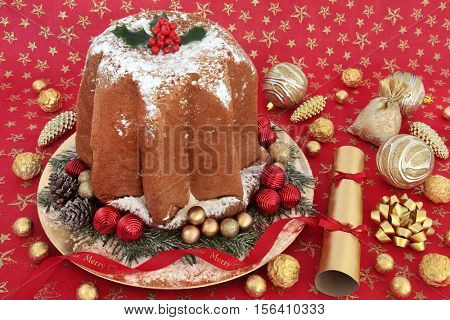 Italian pandoro christmas cake with holly, icing sugar dusting, bauble decorations, cracker and foil wrapped chocolates on a red and gold star festive tablecloth background.