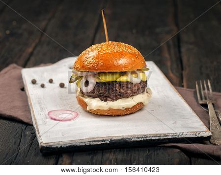 Close up one burger on a white wooden board on dark wooden table