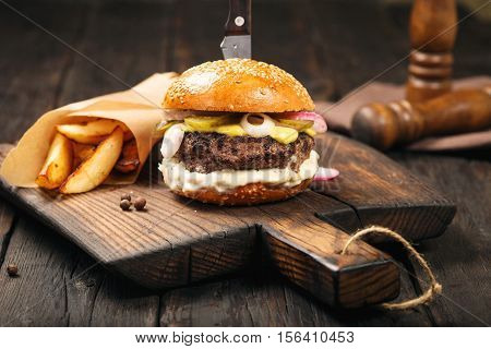 Burger with fries on a old wooden board on dark wooden table close up