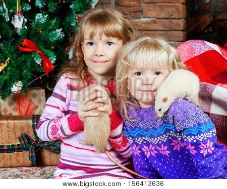 two sisters with their pet rats at home with Christmas tree and presents
