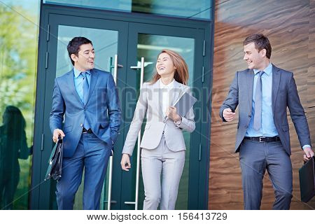 Happy business people leaving office building together