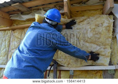 Builder insulating wooden house with mineral rock wool