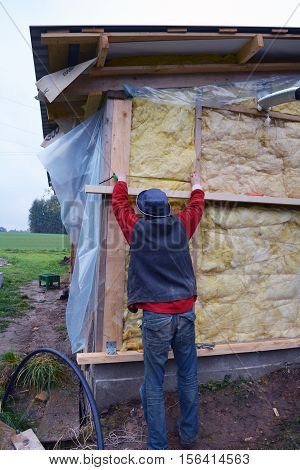 Farm worker insulating wooden house wall with mineral rock wool