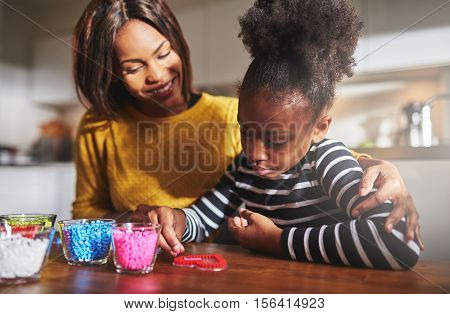 Mother Watching Child Use Craft Beads