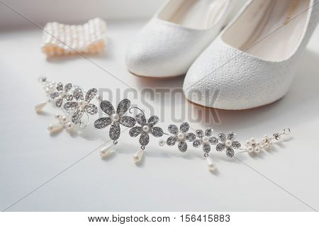 Wedding white shoes and jewelry the bride. Bride dressed before the wedding ceremony