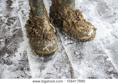 Dirty rubber boots in the snow