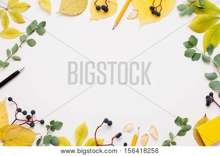 Bright autumn frame on white background, free space for text or advertisement. Yellow and green leaves with blueberry, pen and pencil. Fall inspiration concept