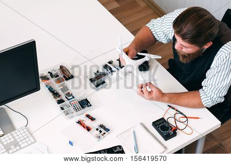 Handyman searching broken drone to find failure reason, top view. New electronics device, unknown technology, problems at work concept