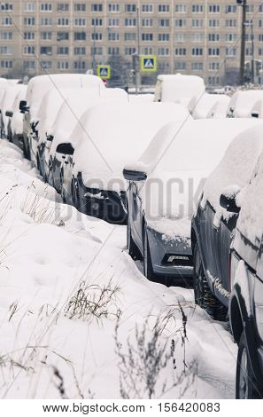 The cars parked at a roadside which are filled up with snow.
