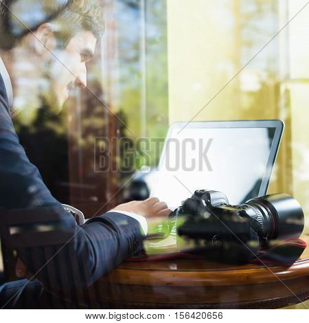 Young man photographer working at cafe, using laptop. His dslr camera at the table. Image through the window