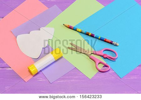How to make paper Christmas card. Step. Colored paper set, scissors, pencil, Christmas tree template, glue stick. Stationery to create a Christmas card. Creative paper art and craft for children