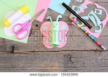 Funny paper butterfly, scissors, marker, glue stick, colored paper sheets and scraps, pencil on old wooden table. Children workplace. Summer children art craft project in kindergarten, camp or home