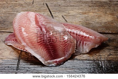 Tilapia Fillets On A Wooden Background