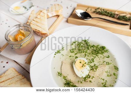 Hot bouillon with toasts and pate top view. Served plate of broth with egg and crusty bread with foie gras. French cuisine, restaurant menu, luxury food , healthy dinner concept