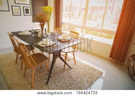 Modern dining room interior with warm light from the sun. Relax day in dining room on free day and no activity. family time with food and enjoy in the family. dining room with table and spoon set.