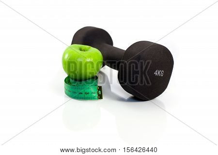 Dumbbell, green apple and measuring tape on a white background. Isolated
