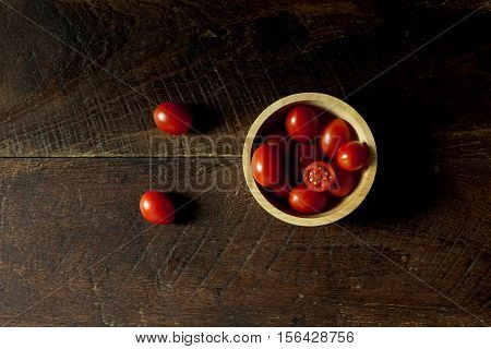 Top view fresh tomato slice and bowl on wood background.