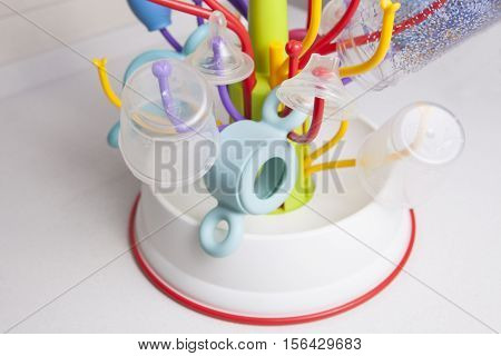 Baby drainer full of plastic tableware objects as baby bottles nasal aspirator milk bowls teats and others