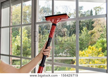 close up of woman cleaning window glass with steam