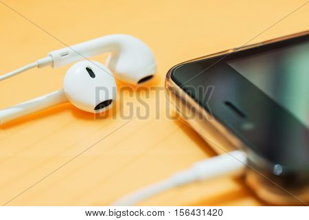 Ear phone into smart phone mobile on blurred orange background