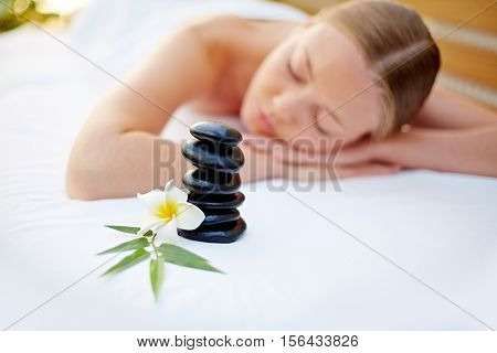 woman lying after stone in spa salon, stones lying in front of her
