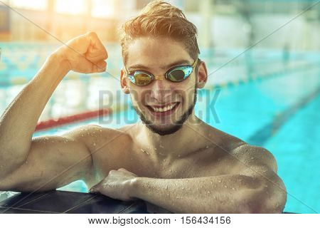 Swimmer man. Portrait of swimming athlete in glasses after training in waterpool.