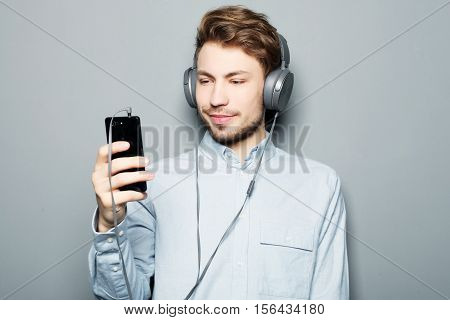 life style, happiness, emotional and people concept: Man holding mobile phone and lictening to music over grey background