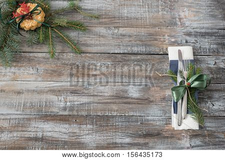 Christmas table place setting with christmas tree branches spoon knife fork and ribbon over wooden table with copy space. Christmas holidays background